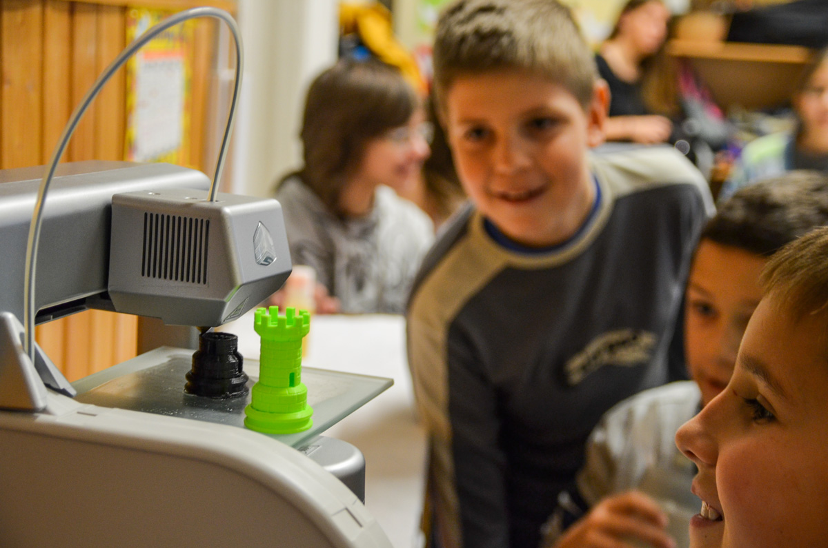 Kids watching a 3D printer