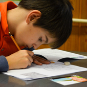 kid writing at his desk