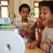 kids watching a 3D printer